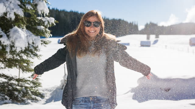 Smiling young woman enjoying winter on a sunny day video