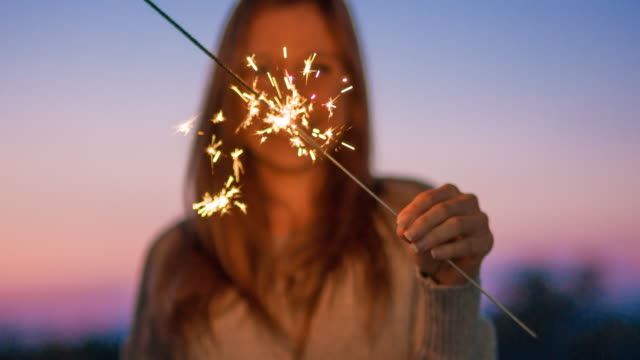 Smiling young woman holding burning sparkler video