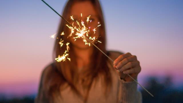 燃える線香花火を持って笑顔の若い女性 ビデオ