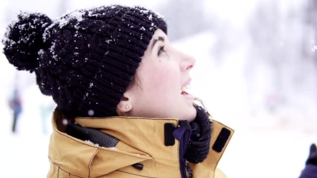 Smiling young woman in bobble hat looking up and enjoying snow fall video