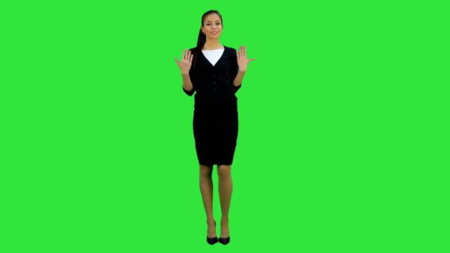 Lachende jonge vrouw in formele slijtage in gesprek met camera en gebaren op een groen scherm, Chromakey video