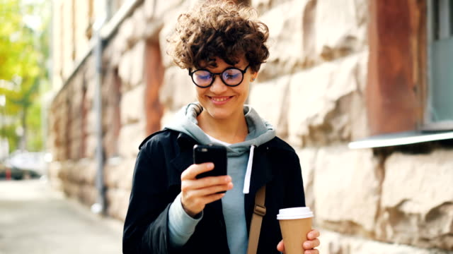 Smiling young woman in glasses is using smartphone looking at screen while walking outdoors in city with to-go coffee. Youth lifestyle, street and technology concept.