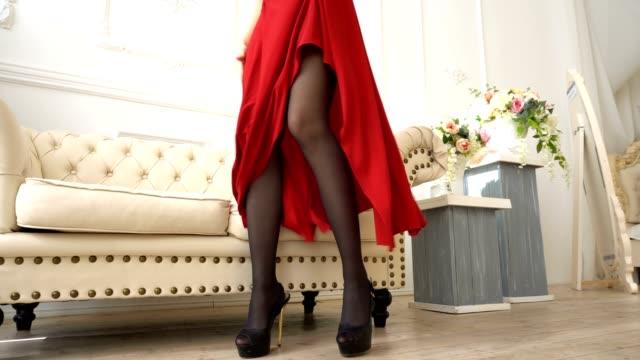 Souriante jeune femme en bas et robe rouge assis sur le canapé. - Vidéo