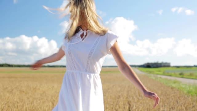 穀物のフィールド上の白いドレスの若い女性を笑顔 - 田舎のライフスタイル点の映像素材/bロール