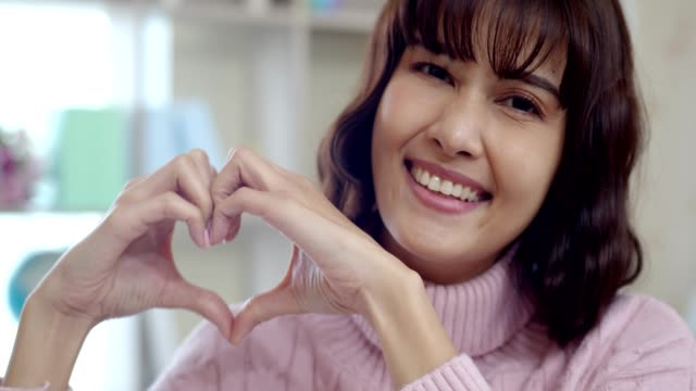 Smiling young woman showing heart with two hands