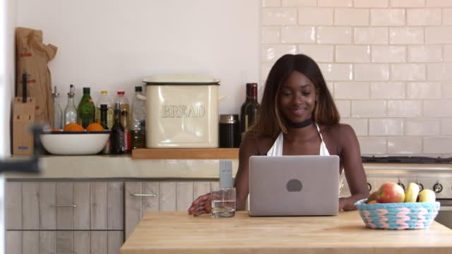 Souriante jeune femme à l'aide d'ordinateur portable dans sa cuisine, abattu le R3D - Vidéo