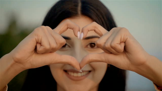 Smiling young woman volunteer showing hands sign heart shape looking at camera at sunset