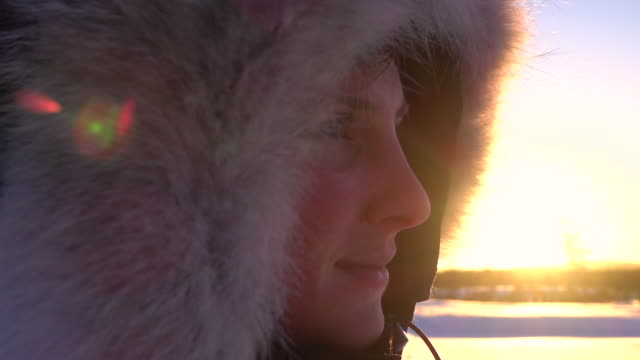 CLOSE UP Smiling young woman with winter jacket hood on head looking into sunset video