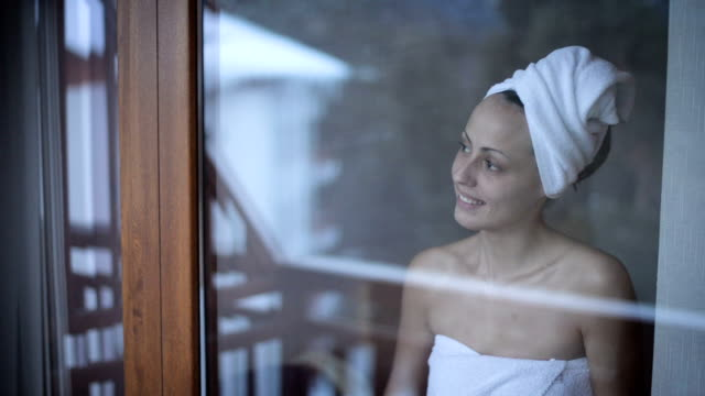 Smiling, young woman wrapped in a towel video