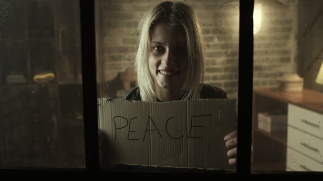 Smiling young women holding peace board video