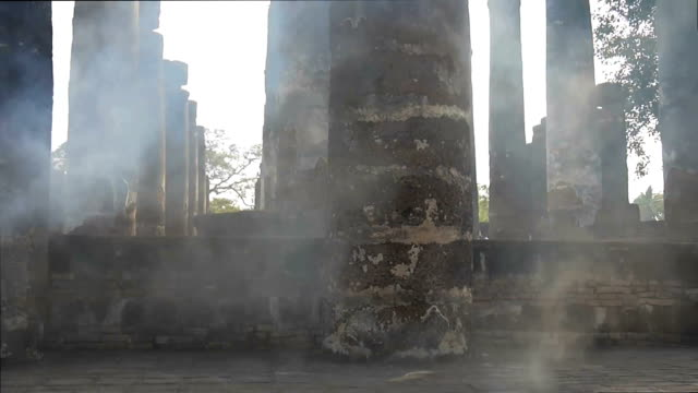 Smoke Across the Pillars Smoke drifts across ancient pillars in the Sukhothai National Park, Thailand sukhothai stock videos & royalty-free footage