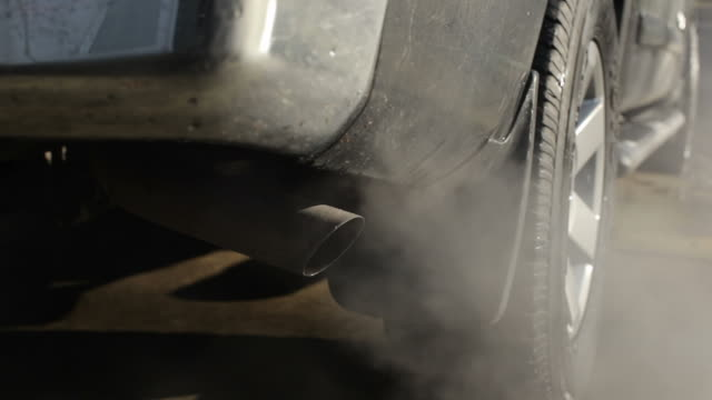 Smoke billows from tail pipe, pollution concept