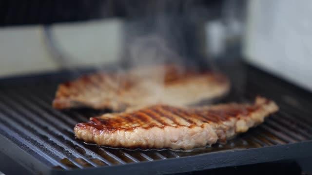 グリルパンのローストステーキから吹く煙 - ブタ点の映像素材/bロール