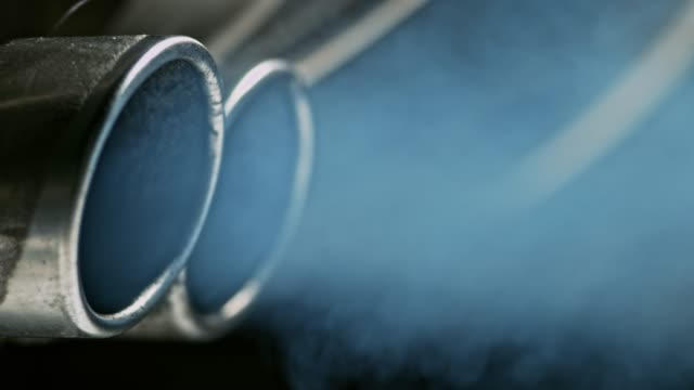 Smoke coming out of the double exhaust pipes of the car