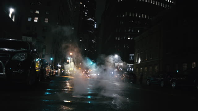 Smoke emitting from street in illuminated city Smoke emitting from street by parked cars. Illuminated buildings in New York city. View is at night. low angle view stock videos & royalty-free footage