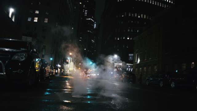 vidéos et rushes de fumée émettant de la rue dans la ville illuminée - vue en contre plongée