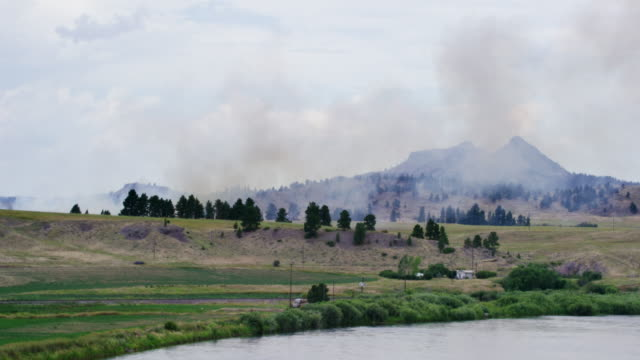 Smoke from a Wildfire in Wyoming Floats through the Air Next to Mountains, Woodland, and a River on a Partly Cloudy Day