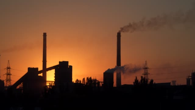 Smoke from pipes of a metallurgical plant at sunrise