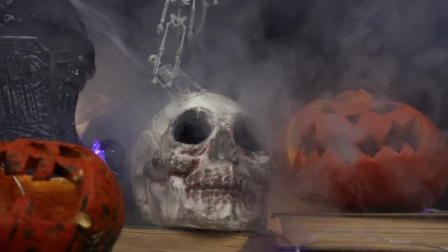 Smoke is blowing at skull, gravestones and pumpkins standing at table