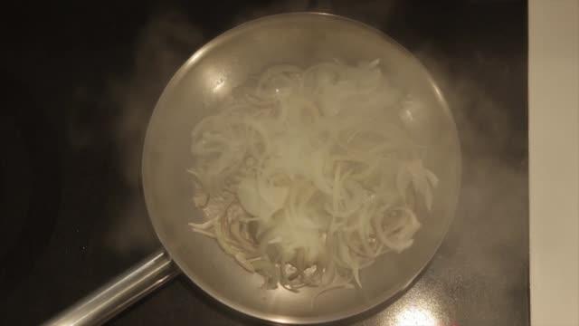 vídeos y material grabado en eventos de stock de fumar cebollas en la sartén - cebolla