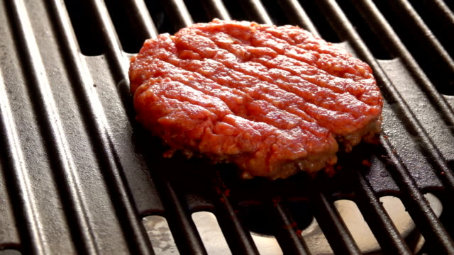 Smoke rises above the cutlet on a hot grill