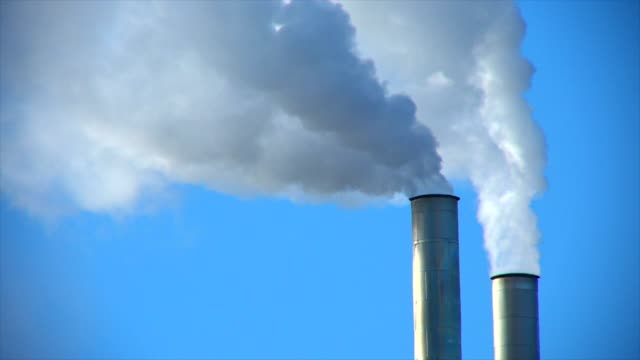 smoke stack emitting against sky - дымоход стоковые видео и кадры b-roll