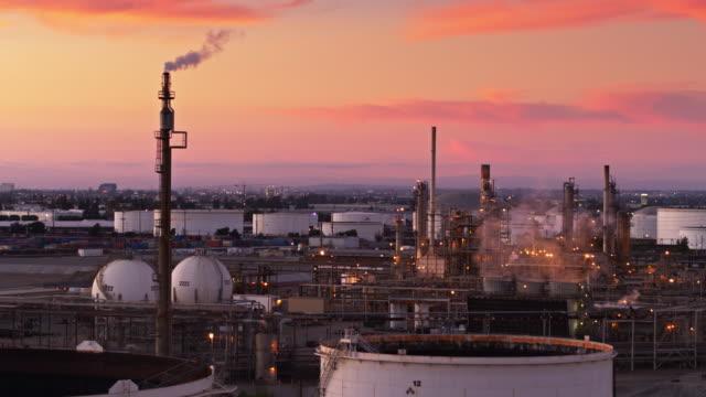 stockvideo's en b-roll-footage met roken stapels in olieraffinaderij tijdens kleurrijke zonsondergang - drone shot - olieraffinaderij