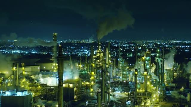 stockvideo's en b-roll-footage met rook stacks ontluchting in olieraffinaderij 's nachts-antenne - raffinaderij