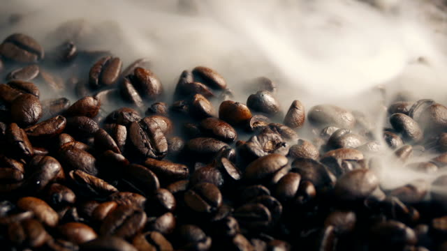 Smoke Wafting Over Roasted Coffee Beans Artistic shot of roasted coffee beans with smoke wafting over them roasted stock videos & royalty-free footage