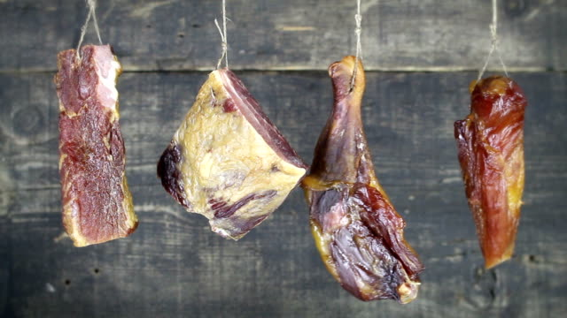 Smoked Chicken Meat Hanging And Swaying Against Wooden Background video