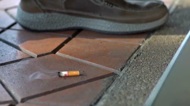 rökaren kasserad cigarettfimp på golvet och släckte - släcka bildbanksvideor och videomaterial från bakom kulisserna