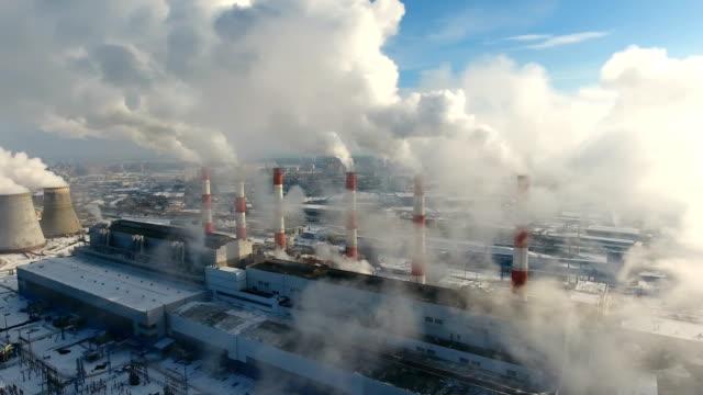 smokestacks at industrial plant polluting atmosphere. winter aerial. - уголь стоковые видео и кадры b-roll