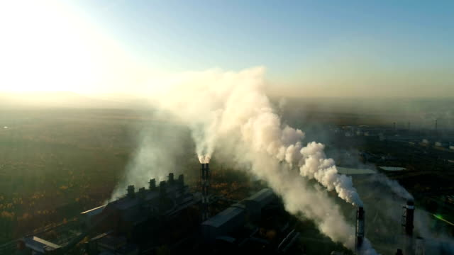 Smoking chimneys of Industrial plant at sunset.