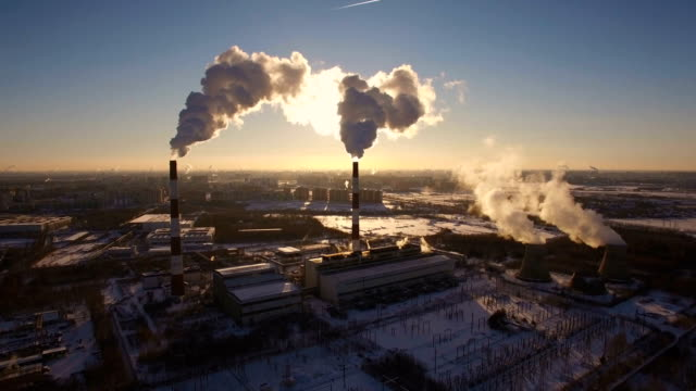 Smoking chimneys power station on sunset background in the winter. Aerial view video