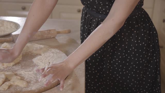 vidéos et rushes de fille fumant dans la robe noire enduit dans la farine pétrir la pâte. concept de cuisine. - rouge à lèvres rouge