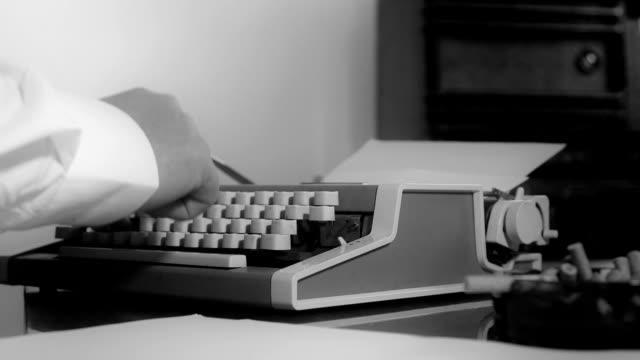 Smoking journalist typing on a portable typewriter video