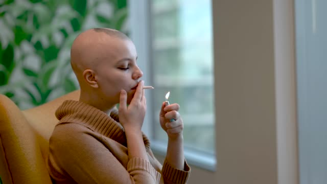 Smoking medical marijuana A young adult female with cancer is lighting up medical marijuana and using it for pain treatment. She is sitting in her lounge room and is in the comfort of her own home. marijuana herbal cannabis stock videos & royalty-free footage