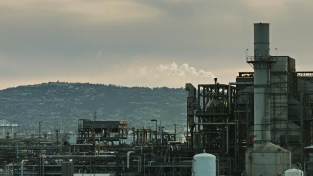 raffineria di petrolio fumante con sfondo suburbano - grandangolo composizione cinematografica video stock e b–roll