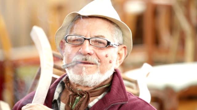 Smoking senior artisan working in small shop video HD video