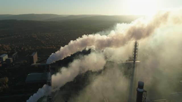 rauchende rauchschwaden der industrieanlage bei sonnenuntergang - aluminium stock-videos und b-roll-filmmaterial