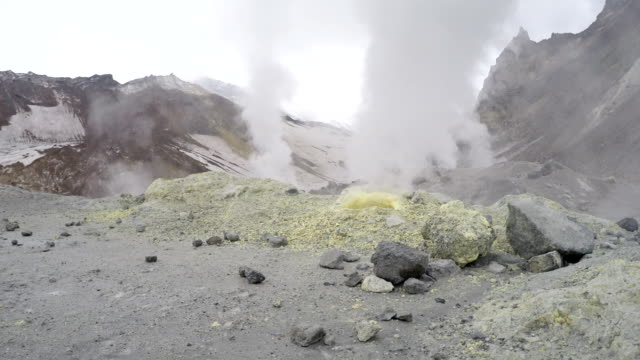 smoking sulfuric fumarole in crater active volcano - emettere video stock e b–roll