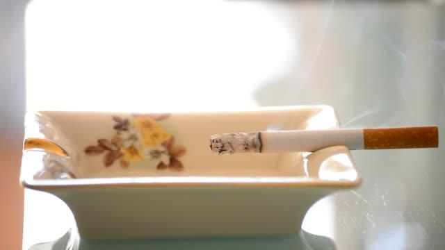 Smoking tobacco cigarette burning in ashtray video