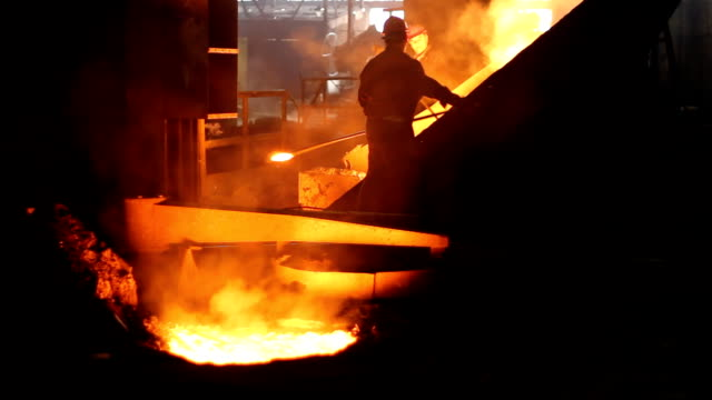 Smoky and Hard working Environment Hard work in the foundry, worker controlling iron smelting in furnaces, too hot and smoky working environment, two video shots in one video footage foundry stock videos & royalty-free footage
