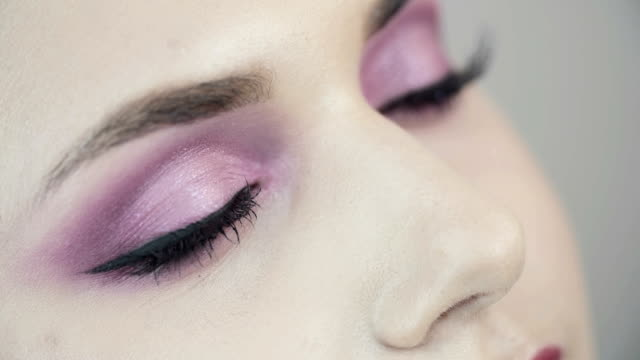 Smoky eyes. Pink make up. Smoky eyes. Pink make up. Close-up of beautiful eyes of a girl with pink shades. The girl opens her eyes. Looks at up. Clear skin. eyeliner stock videos & royalty-free footage