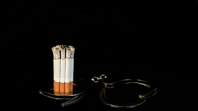 smoldering cigarette in handcuffs video