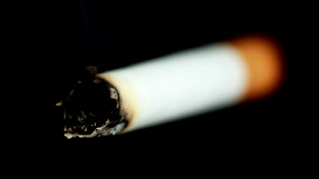 Smoldering Cigarette, isolated on black Extreme macro/closeup of a burning cigarette, isolated on a black background. emphysema stock videos & royalty-free footage
