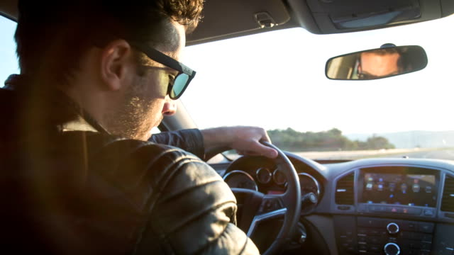 Smooth Driving Handsome young man driving a sports car. He is wearing a leather jacket and sunglasses. luxury car stock videos & royalty-free footage