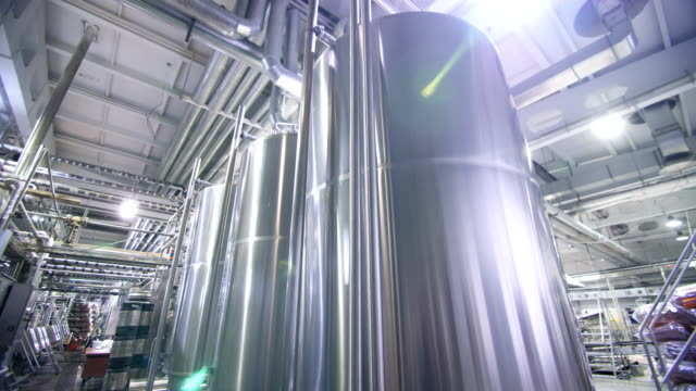 Smooth panorama over steel tanks at the brewery. - video