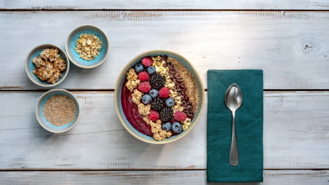 vídeos de stock e filmes b-roll de smoothie bowl with with berry fruits, nuts and granola - granola