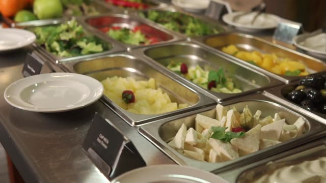 smorgasbord with salads on dining in a restaurant, panorama of dishes - фуршет стоковые видео и кадры b-roll